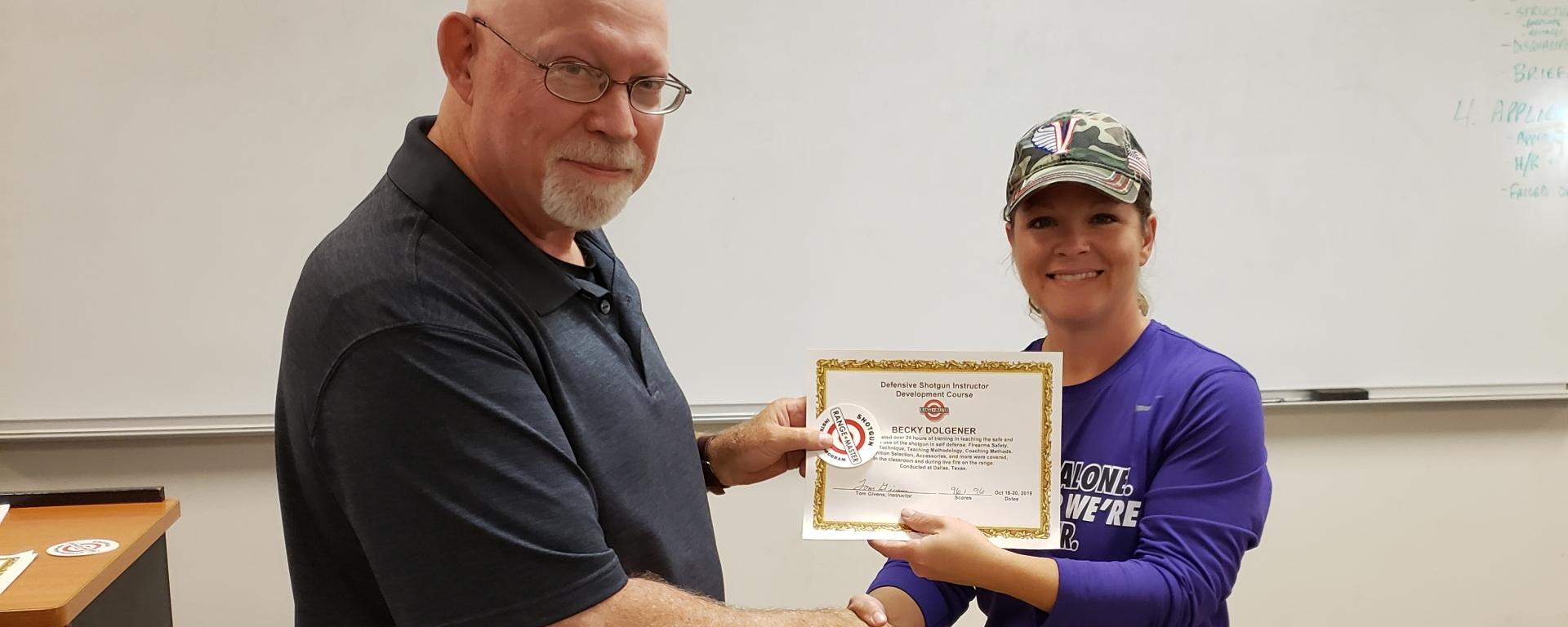 Becky receives a Rangemaster Defensive Shotgun Instructor certificate from Tom Givens