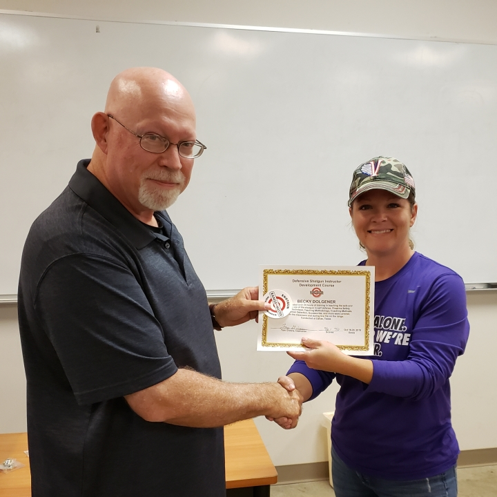 Becky receives a Rangemaster Defensive Shotgun Instructor certificate from Tom Givens